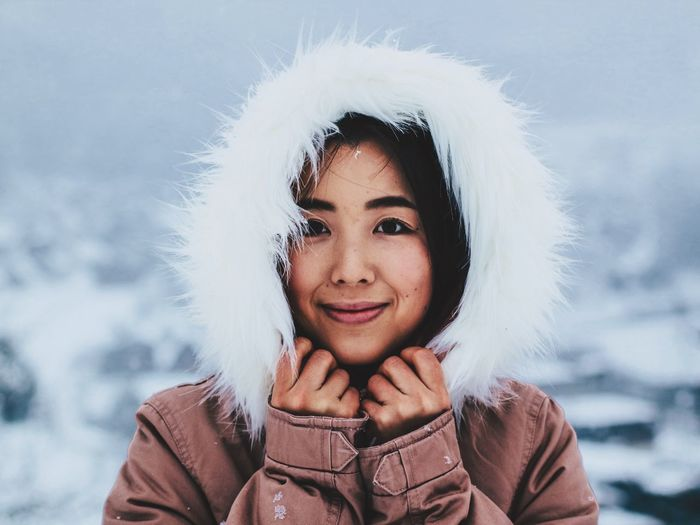 Portrait of smiling young woman in warm cloths during winter