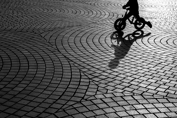 Low section of boy riding bicycle on street