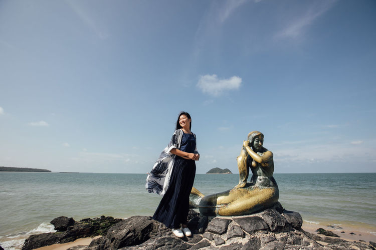 Woman standing by statue at beach against sky
