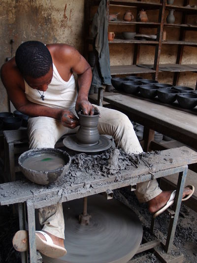 Making of handcrafts with clay and wheel Business Stories Wheel Bussiness Craftsperson Creation Day Expertise Handmade Human Hand Indoors  Making Manual Worker Men Motion Occupation One Person Pottery Pottery Art Profession Professional Occupation Real People Skill  Vocation Working Workshop