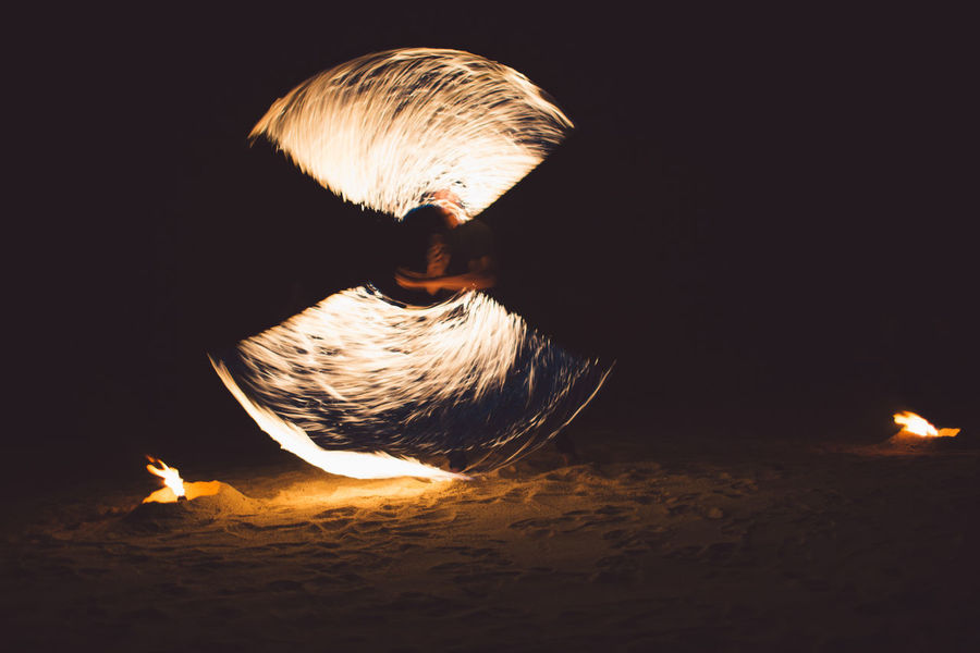 Fire Burning Fire - Natural Phenomenon Flame Night Heat - Temperature Motion Nature Glowing One Person Land Illuminated Beach Men Outdoors Blurred Motion Leisure Activity Lifestyles Real People Dark Bonfire Black Background