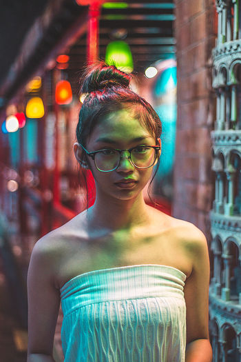 Portrait of teenage girl wearing eyeglasses at night