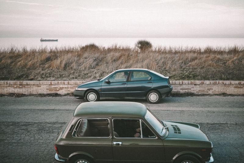 Vintage car on road by land against sky