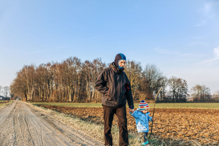 Grandfather with granddaughter walking on country road