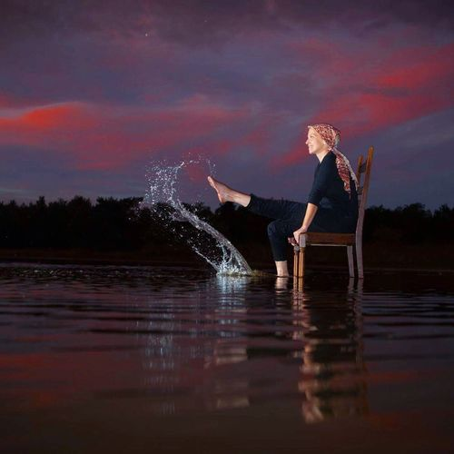 Beautiful young blonde woman sitting on a chair in the water of a lake around Dusk, sunset, and playfully Water Full Length One Person Waterfront Lake Reflection Real People Side View Motion Young Adult Sky Outdoors Young Women Lifestyles Sunset Nature Blond Hair Beauty In Nature Night Tree kicking her feet out of the water