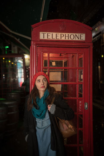 Woman standing against telephone booth