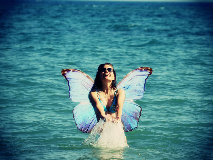 Young woman with butterfly wings, smiling