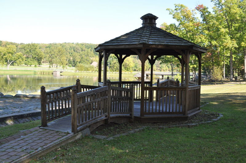 Wood Gazebo in a Park by a Lake Architecture Beauty In Nature Building Exterior Built Structure Clear Sky Gazebo Lake Nature No People Outdoors