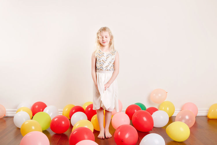 Portrait of smiling woman with balloons against white background