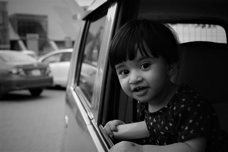 Portrait of cute girl in car