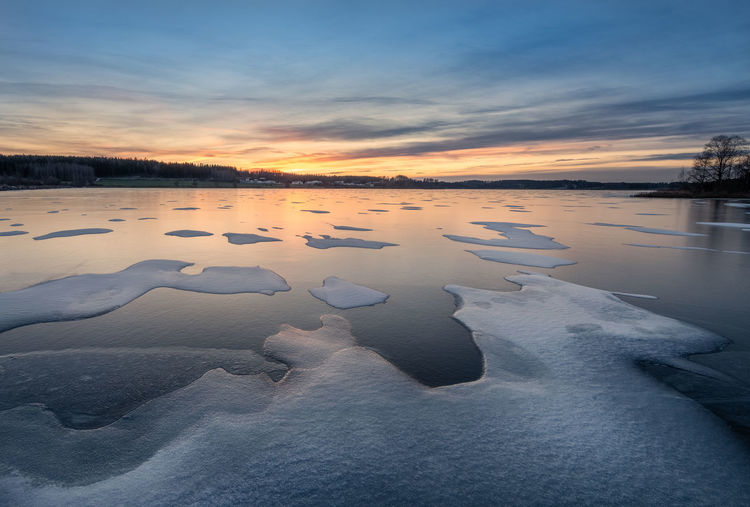 Scenic winter landscape with frozen lake, sunset and beautiful evening light in Finland Sunset Scenics - Nature Beauty In Nature Tranquility Tranquil Scene Cloud - Sky Nature Idyllic Reflection Cold Temperature Ice Winter No People Frozen Frost Snow Coldness Lake Nature Landscape Finland Tranquility Twilight Icy Structure