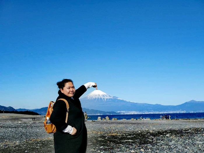 Woman pointing at mount fuji against blue sky