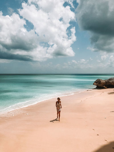 Woman Walking At Beach Against Cloudy Sky