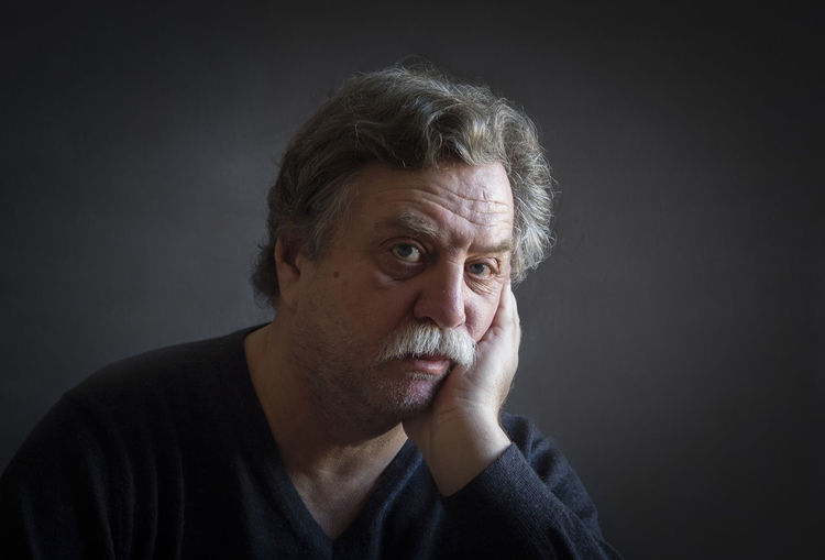 Portrait Of Thoughtful Man Against Black Background