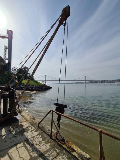 Sailboat on bridge over sea against sky