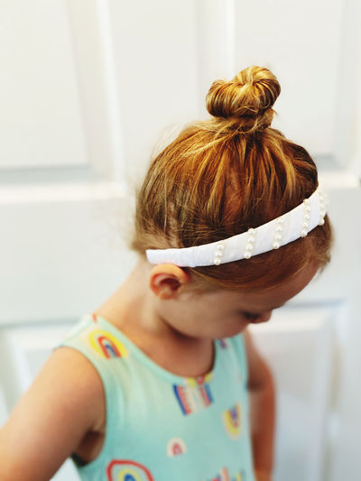 Side view of little girl wearing her hair in a bun with head band on