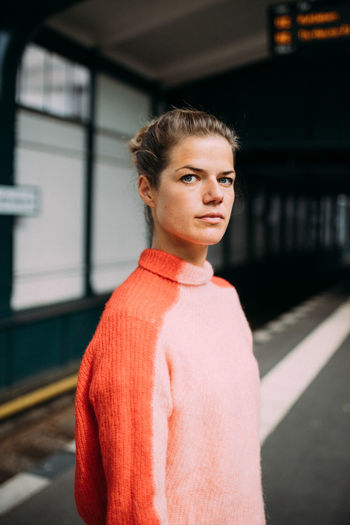 Portrait of woman standing against orange wall