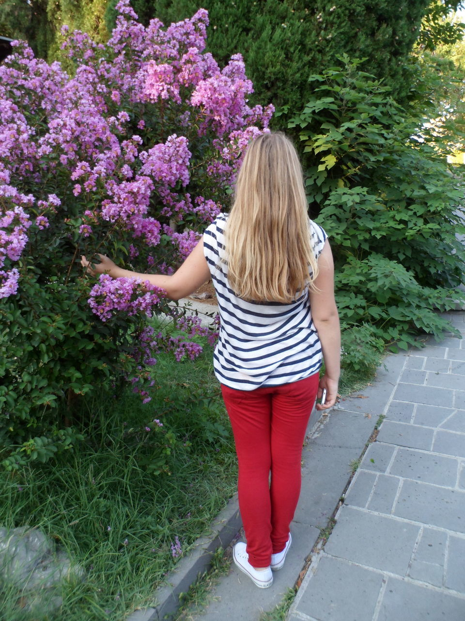 rear view, blond hair, one person, flower, full length, casual clothing, day, real people, plant, only women, outdoors, growth, standing, one woman only, leisure activity, young adult, nature, one young woman only, young women, beautiful woman, adults only, people, adult