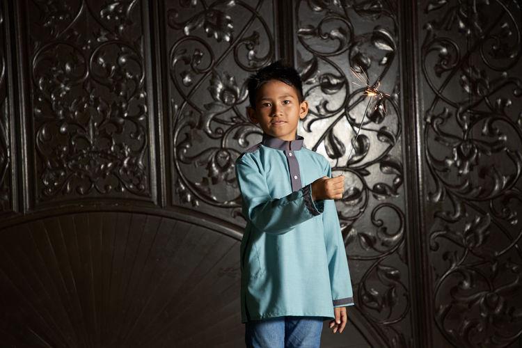 Malay boy playing fireworks sparkler during ramadan festival