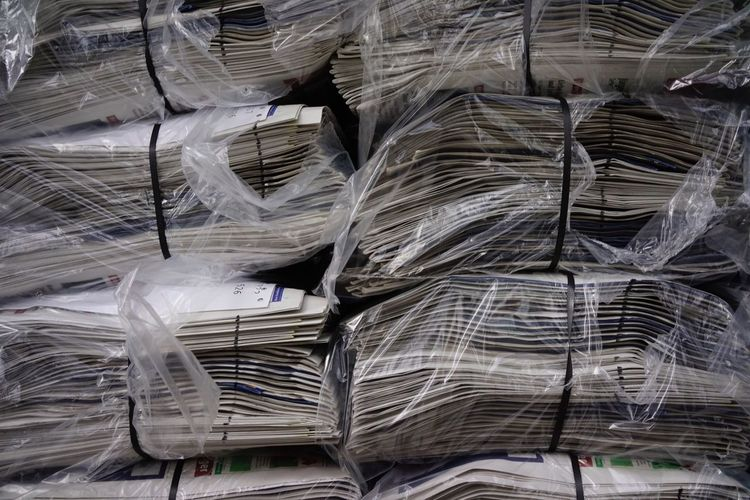 Full Frame Shot Of Stacked Newspapers Wrapped In Plastic