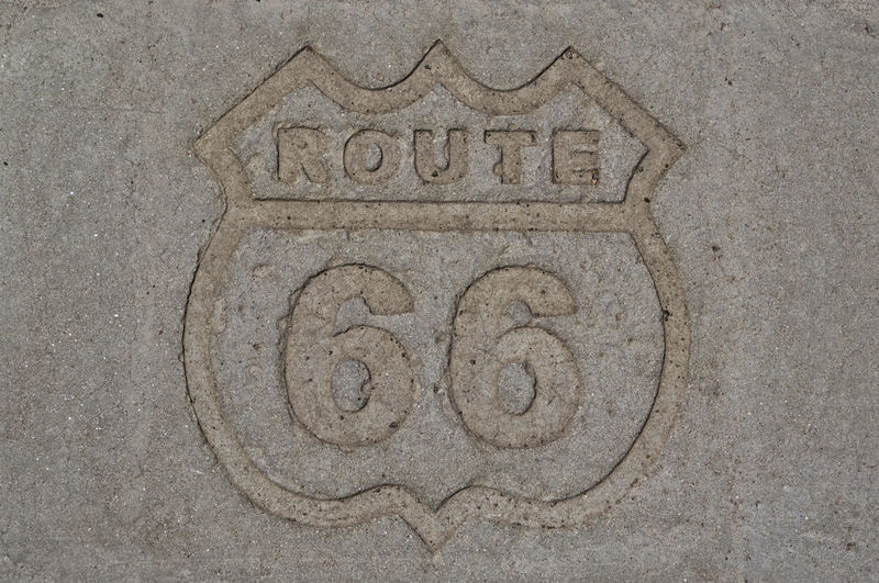 Stone sign of the famous and historic route 66, the highway that crosses the USA from the west coast to the east coast. Abstract rectangular background. Concept for travelling and adventure 66 American Famous Freedom Road Rock Sign Signage USA Wall Adventure America Coast Drive Grunge Highway Hostorical Information Message Old Route Stone Street Symbol West