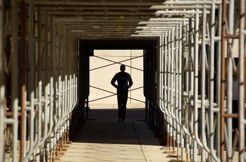 Front View Of Man Walking On Elevated Walkway