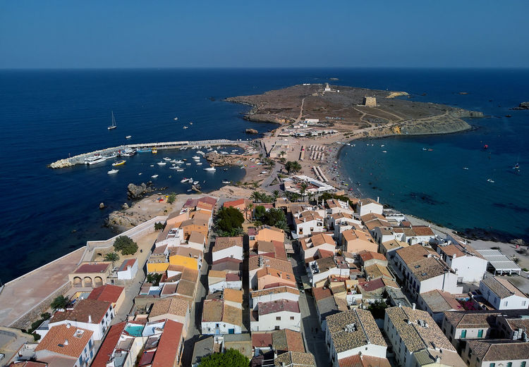 Aerial view of Tabarca Island. Harbor marina, moored vessels and pebble beach. Travellers, vacationers sunbathing and swimming in the Mediterranean Sea. Popular travel destinations at summer. Spain Aerial Shot Alicante Province Spain Harbor Mediterranean Sea Moored Boats SPAIN TOWNSCAPE Tabarca's Island Aerial Aerial Landscape Aerial Photography Aerial View Bay Europe Famous Place High Angle View Island Landscape Nature Sea Summer Sunny Day Tabarca Town Travel Destinations