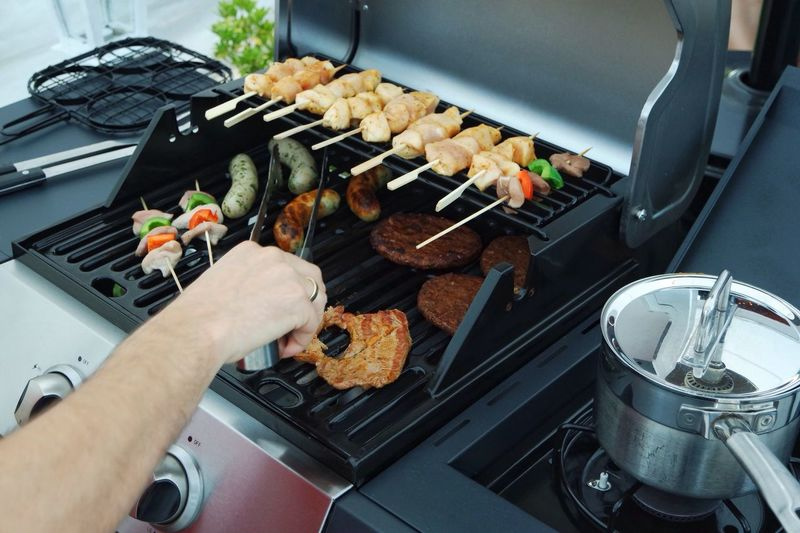 Cropped Hand Of Man Grilling Meat On Barbecue Grill In Yard