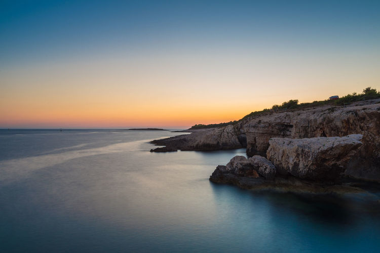 Long exposure coastline Cliff Cloudless Coastline Filter Horizon Over Water Long Exposure Majestic Nature Nd Ocean Outdoors Remote Rock Scenics Sea Seascape Shore Summer Sundown Sunset Tranquility Water