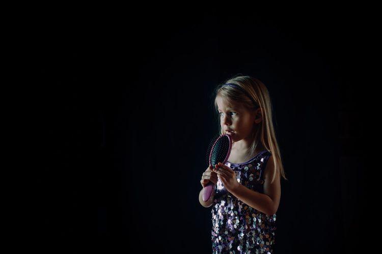 Girl standing against black background