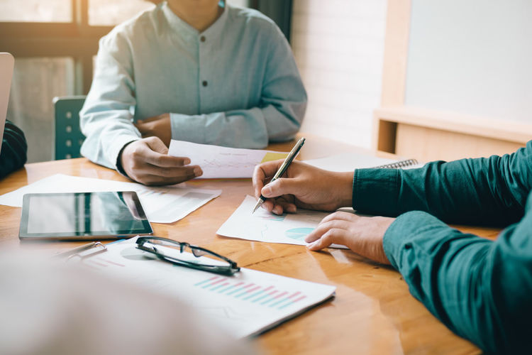 Adult Coworker Document Holding Human Hand Indoors  Males  Men Midsection Occupation Paper Paperwork Pen People Real People Selective Focus Sitting Table Two People Working Writing