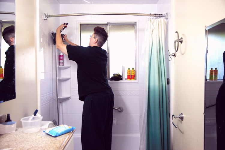 Rear View Of Woman Fixing Shower Head In Bathroom At Home
