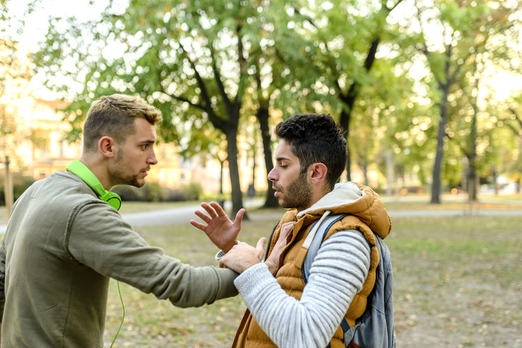 Side view of friends arguing in park during autumn