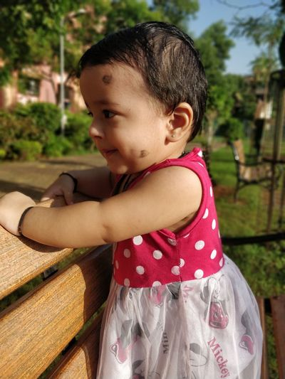 Close-Up Of Cute Baby Girl Looking Away On Bench In Park