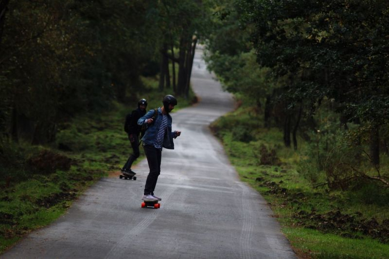 Man and woman skateboarding on road