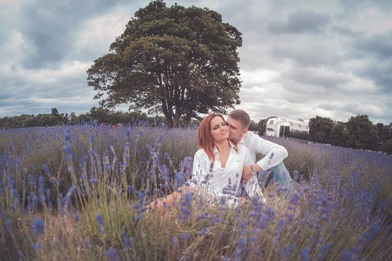 Couple cuddling amidst blooming lavenders