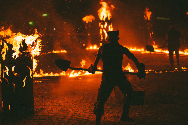 Men throwing dirt in fire at night