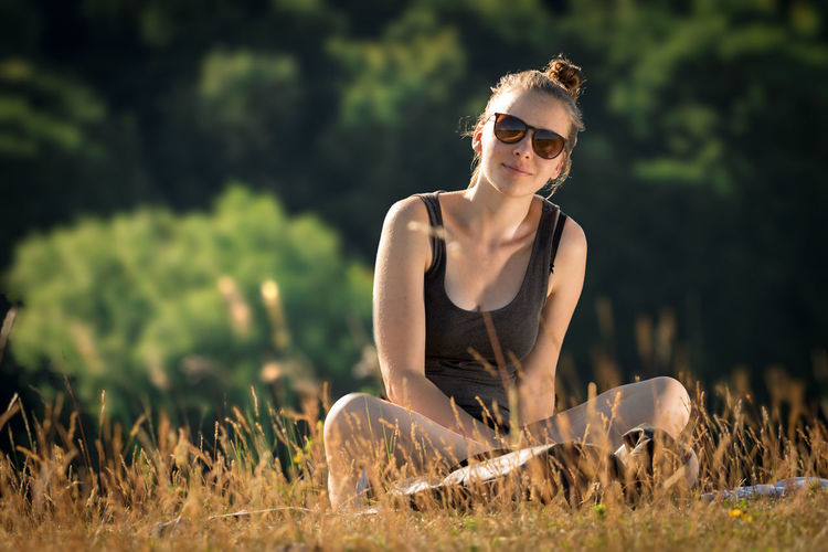 Young Woman Wearing Sunglasses Sitting On Field