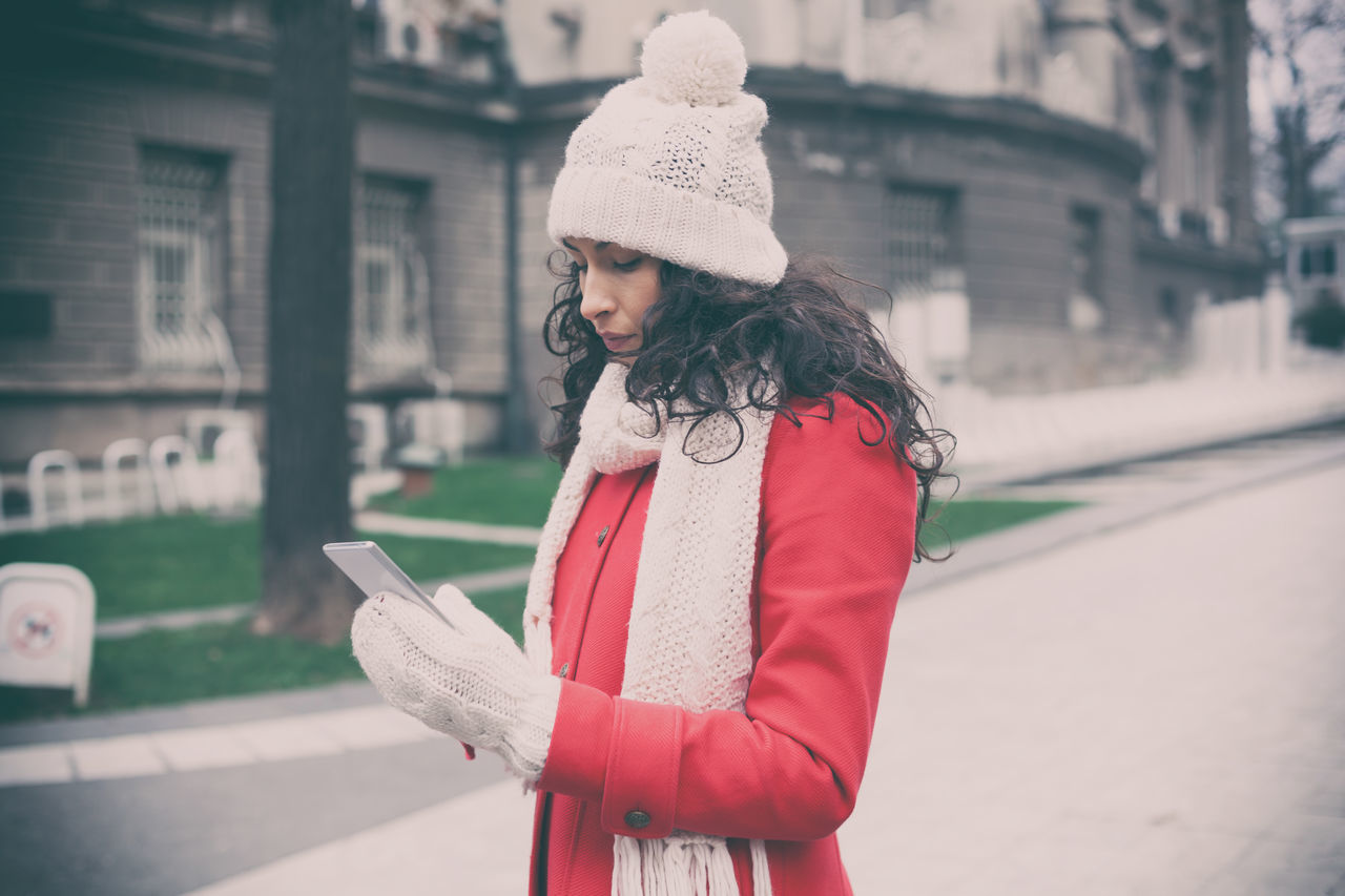 clothing, city, hat, one person, architecture, winter, street, focus on foreground, standing, warm clothing, built structure, real people, women, building exterior, day, lifestyles, waist up, knit hat, adult, scarf, outdoors, beautiful woman