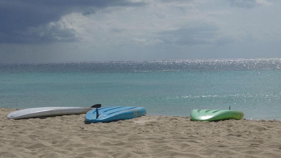 Surfboards on beach against sky