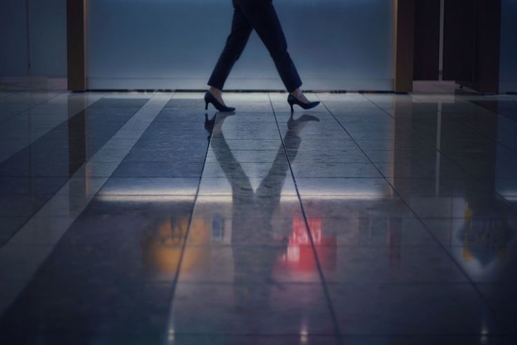 Low section of woman walking on tiled floor