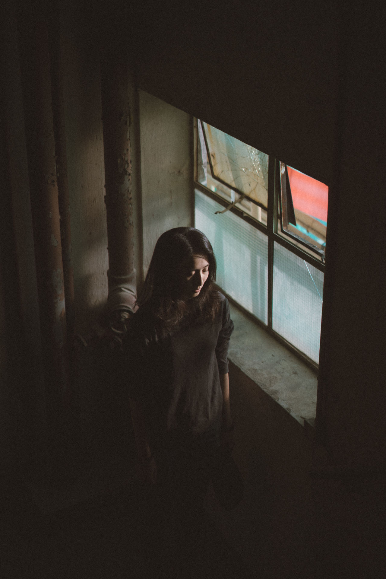 WOMAN LOOKING THROUGH WINDOW IN HOME