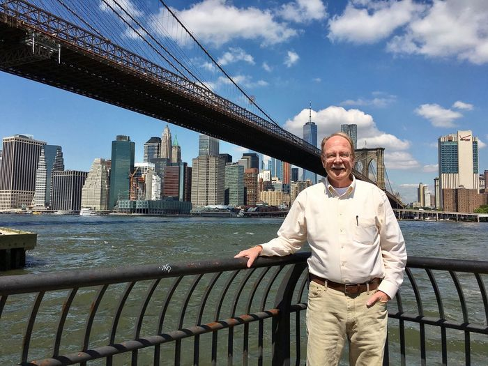 Portrait of senior man standing against brooklyn bridge and one world trade center