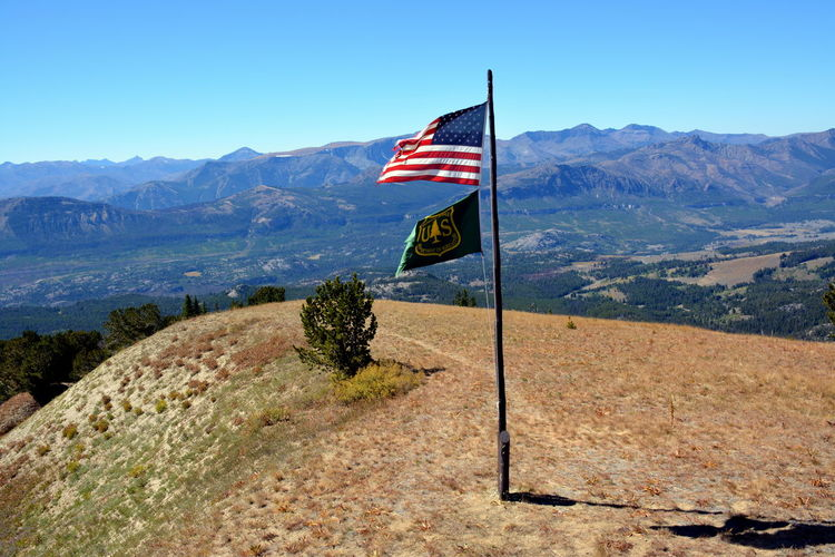 American flag waving at clay butte lookout against mountains