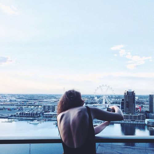 Rear view of woman photographing cityscape against sky