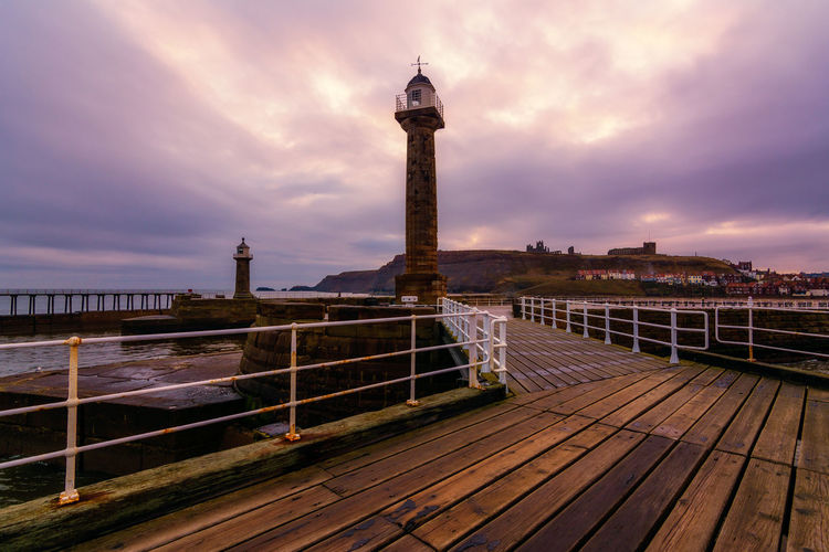 Whitby West Pier Light in Yorkshire Dracula Lighthouse Moody Sky West Pier Light Whitby Whitby Abbey Whitby Harbour Whitby North Yorkshire Architecture Beauty In Nature Building Exterior Built Structure Cloud - Sky Coast Day Historic No People Old Lighthouse Outdoors Planks Seaside Town Sky West Pier Wooden Walkway