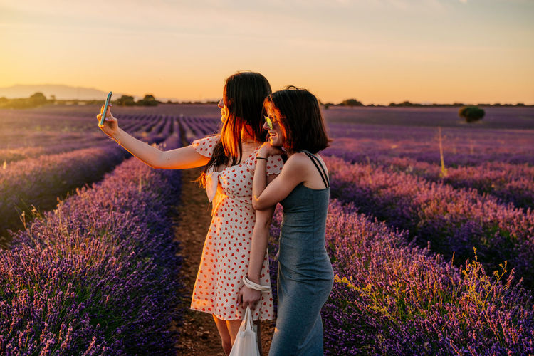 Women taking selfie while standing on field against sky during sunset