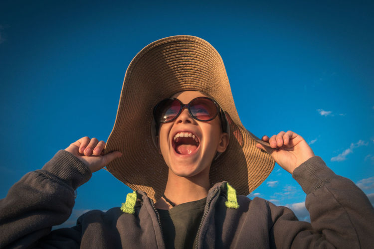 Beautiful boy with big straw woman hat and big sunglasses screaming happy and carefree in the wind Blue sky clouds gray sweatshirt with yellow fluo laces hands keep the hat from the wind From below Headshot Portrait Hat Sky One Person Front View Lifestyles Real People Clothing Low Angle View Young Adult Leisure Activity Emotion Blue Nature Day Sunlight Looking At Camera Mouth Open Outdoors Hairstyle Smiling Face Sunglasses Happyness