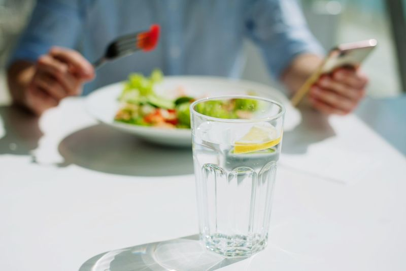 young guy eating a salad Food And Drink Glass Focus On Foreground Holding Human Hand Midsection Table Adult Household Equipment Refreshment Food Freshness Plate Hand One Person Real People Indoors  Men Business Human Body Part