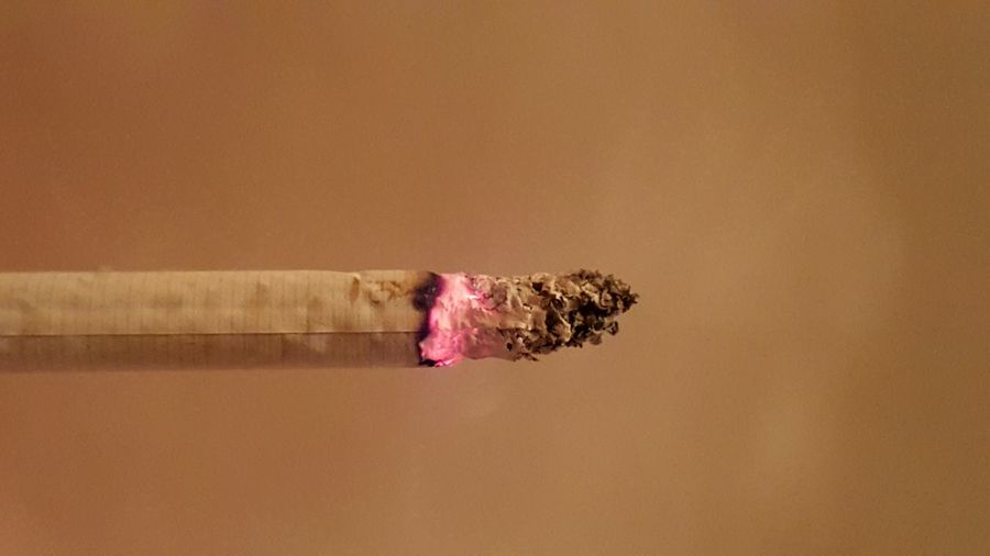 Close-Up Of Burning Cigarette Against Beige Wall